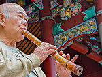 Flutist playing his flute in the Temple of Confucius in Taipei, Taiwan