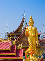 Figure of Buddha against the Buddhist Palace in Xishuangbanna, China