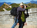 Tourist photographing scenic beauty opening out of the height of the Great Wall of China