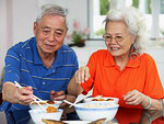 Chinese adult couple having traditional family dinner